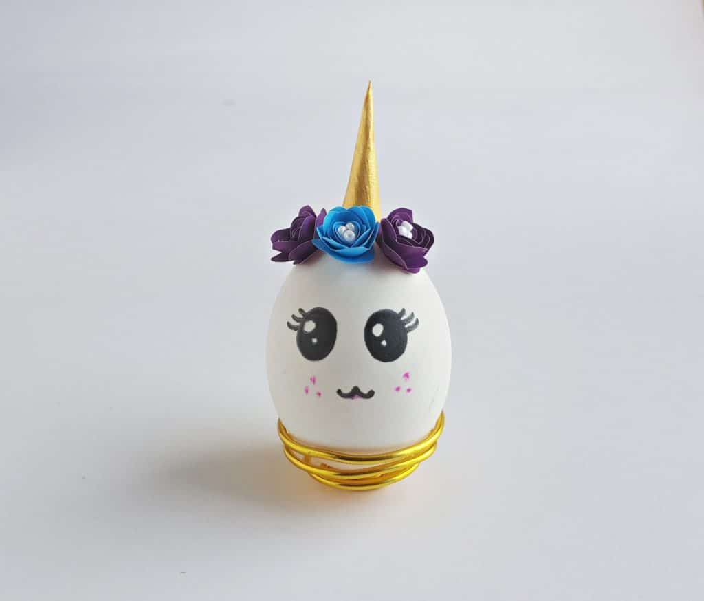 unicorn egg with crown of purple and blue flowers and gold horn