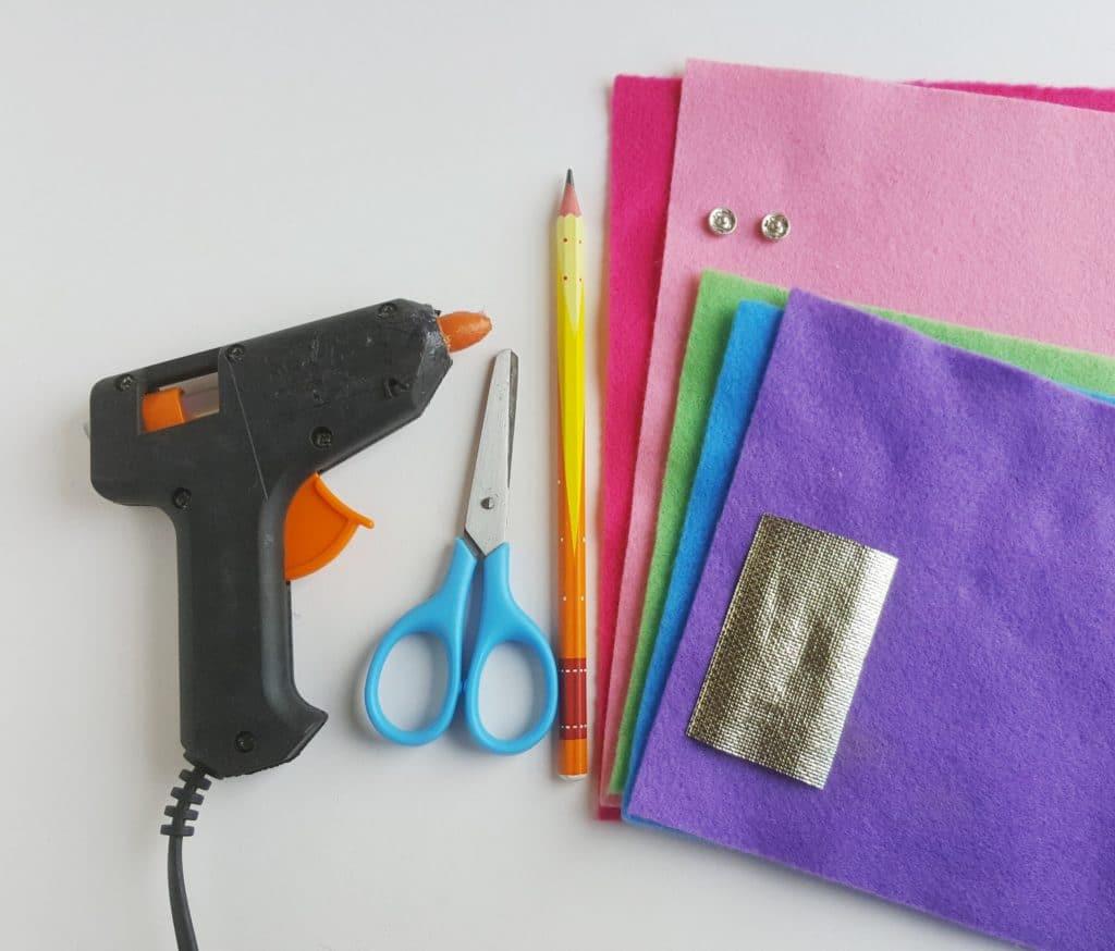 unicorn pencil case supplies including a glue gun and fabric