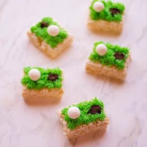 golf rice krispies with green icing, white golf ball and hole with cookie crumbs