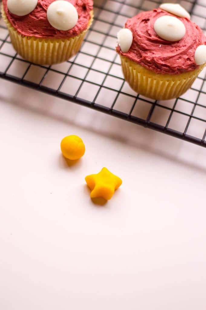 small yellow starts with mario cupcakes in background with red icing on a cooling rack