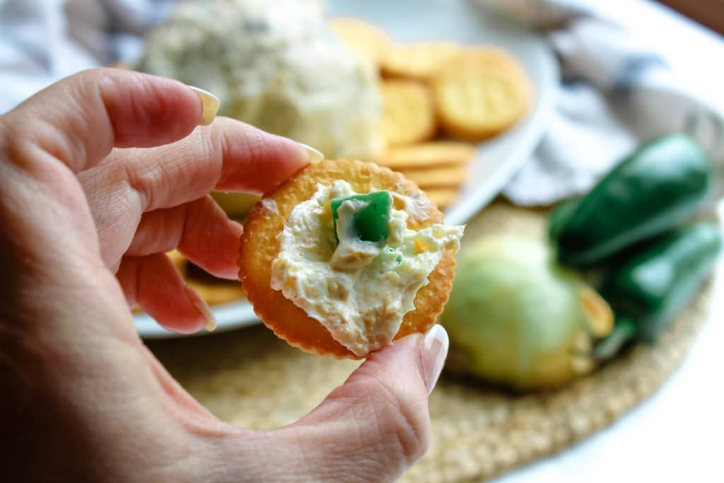 holding a cracker with jalapeno dip on it