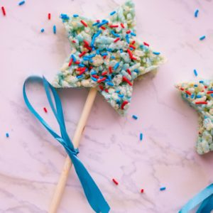 patriotic rice krispies treats on a stick with blue ribbon