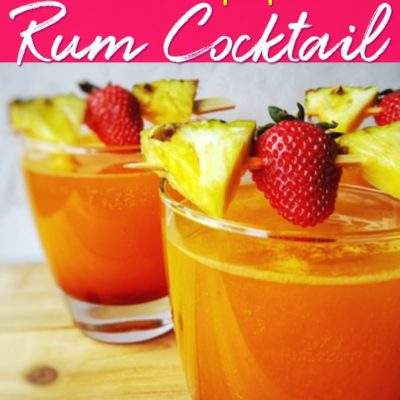 two pineapple rum cocktail glasses with pineapple and strawberries attached to a skewer on top