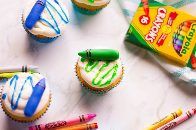 fully decorated crayon cupcakes on a baking sheet next to crayola crayons box