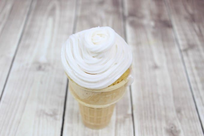 overhead view of ice cream cone cupcake with vanilla icing on top
