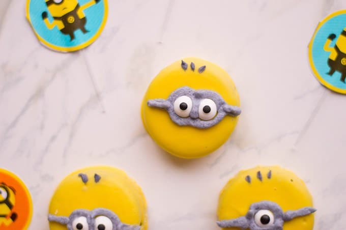 fully completed minion oreos on a countertop next to minion toys
