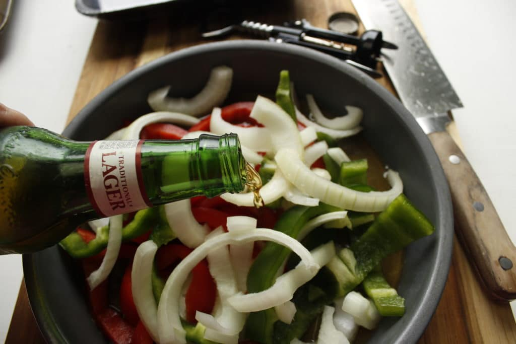 pouring yuengling beer into metal dish with peppers and onions