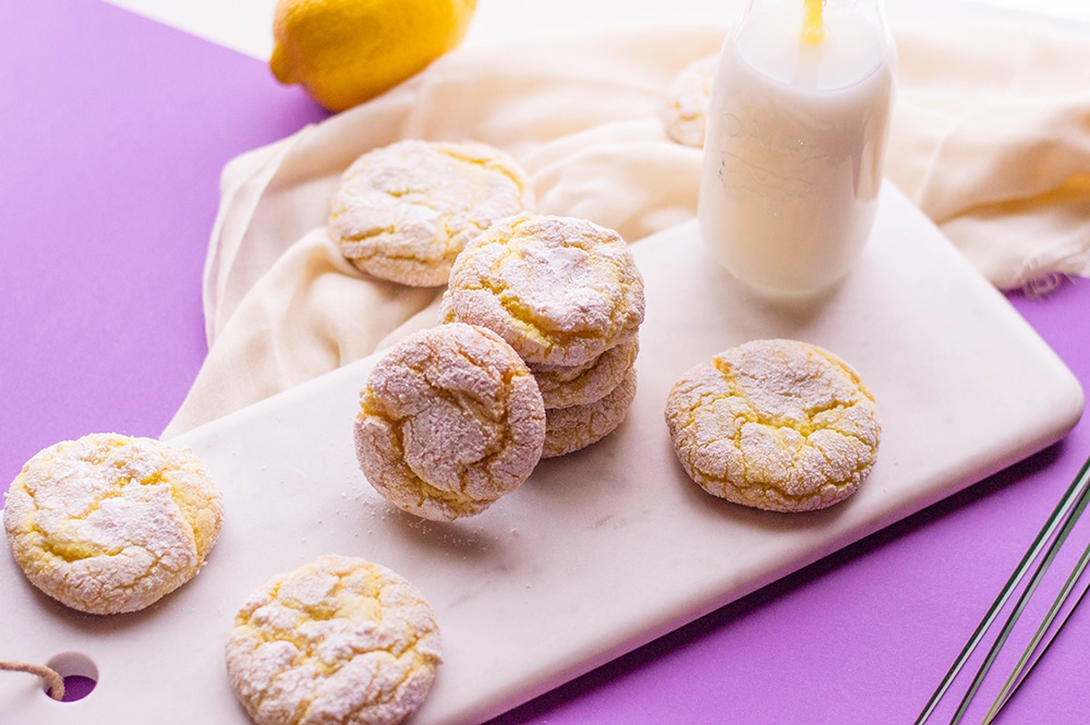 lemon crinkle cookies on a cutting board next to a container of milk