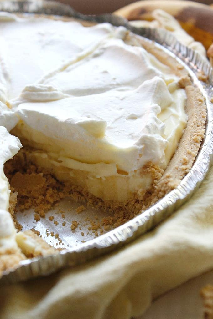 closeup of no bake banana cream pie with one slice missing