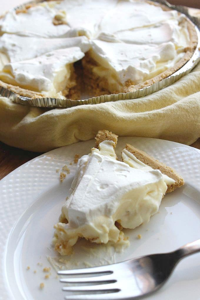 slice of no bake banana cream pie sitting on a white plate next to a fork with pie in background