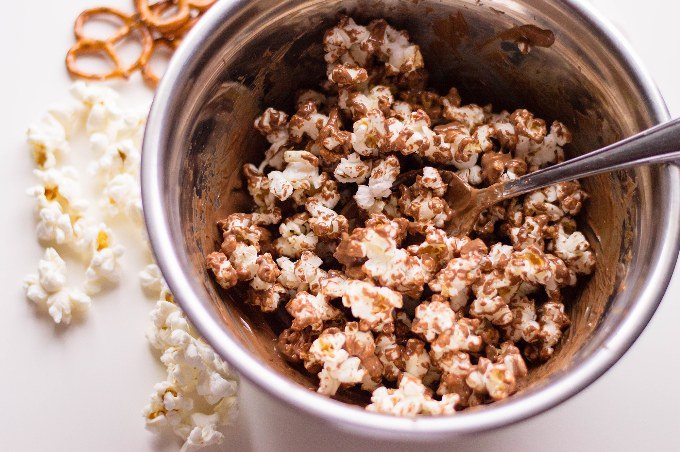 sweet and salty popcorn in a mixing bowl with spoon sticking out