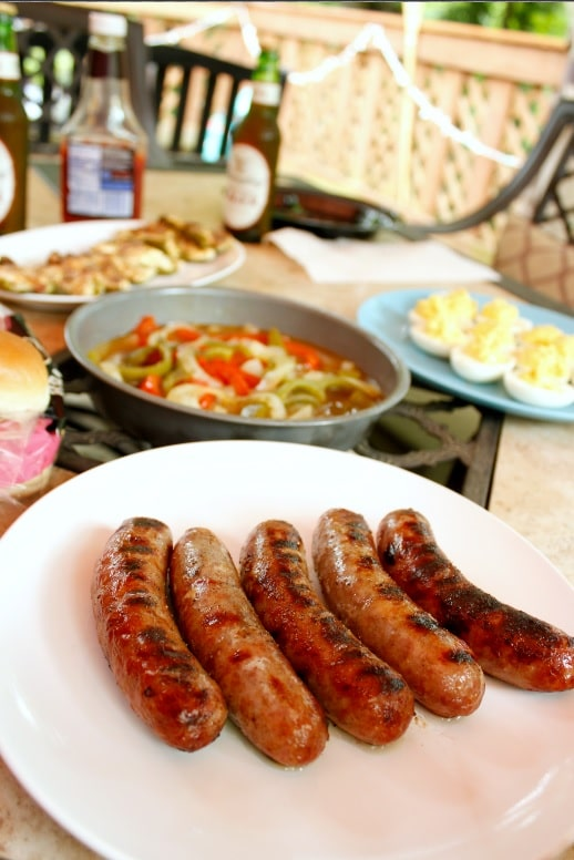 yuengling brats on plate with grilled peppers in background