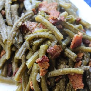 vertical shot of green beans with bacon on white plate