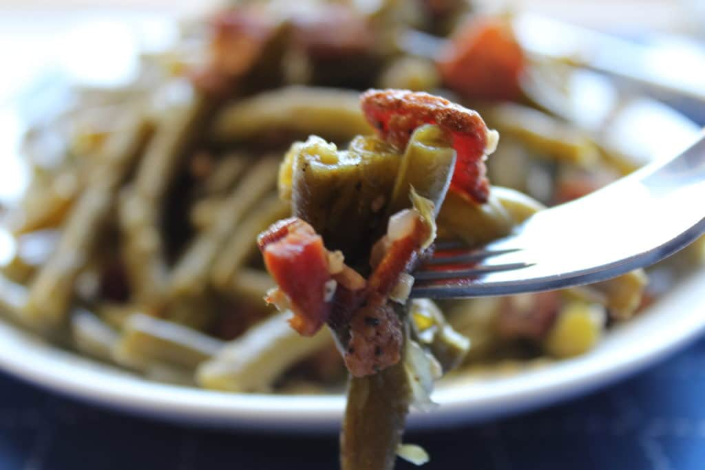close up shot of green beans with bacon and onions on fork