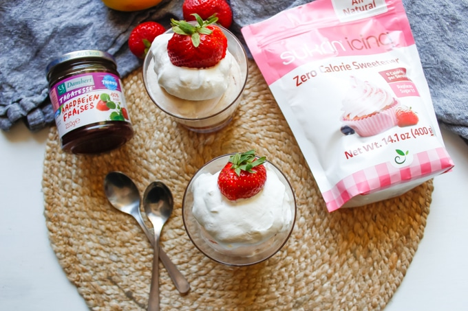 Jars of strawberry fluff layered with whipped cream and garnished with strawberries next to Sukrin Icing and Sukrin Strawberry Jam