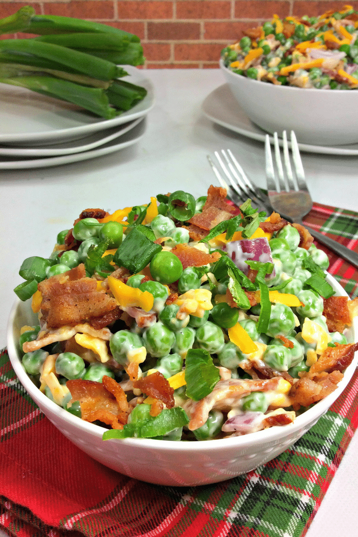 Sweet pea salad recipe with bacon in a bowl with two forks