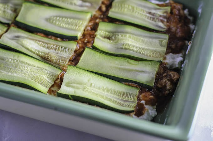 In a 9x13 baking dish, layer the bottom row with zucchini noodles. Spread the cheese mixture over the zucchini and add a layer of the meat sauce. Repeat these steps to create the layers in your zucchini lasagna. Top with mozzarella cheese. Cover dish with foil.