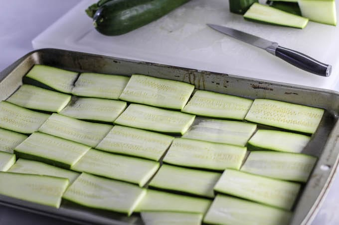Slice the zucchini lengthwise. Lay the zucchini flat on a cookie sheet and bake in the oven on 375 for 15 minutes. This is a critical step to make sure you bake out most of the liquid.