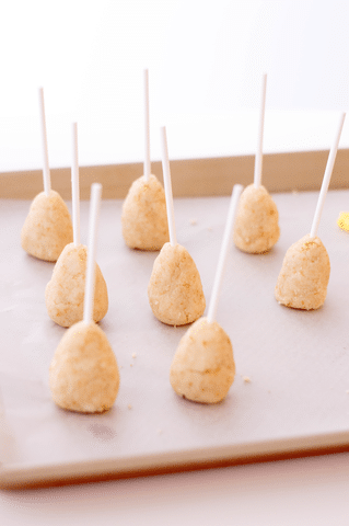 cone shaped cake balls with lollipop sticks on baking sheet