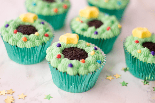 cupcakes with green icing and candy pieces
