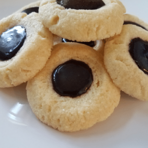 thumbprint cookies with chocolate icing on white plate