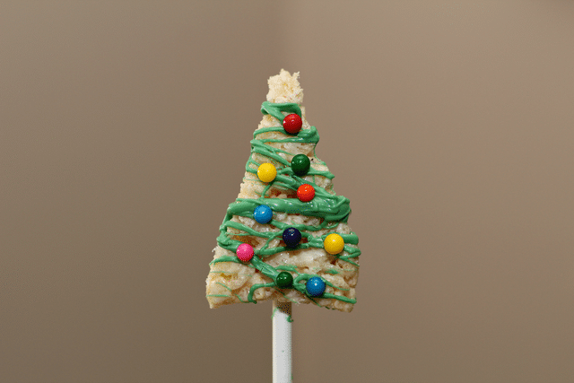 christmas tree shaped rice krispie treats with green icing and candies