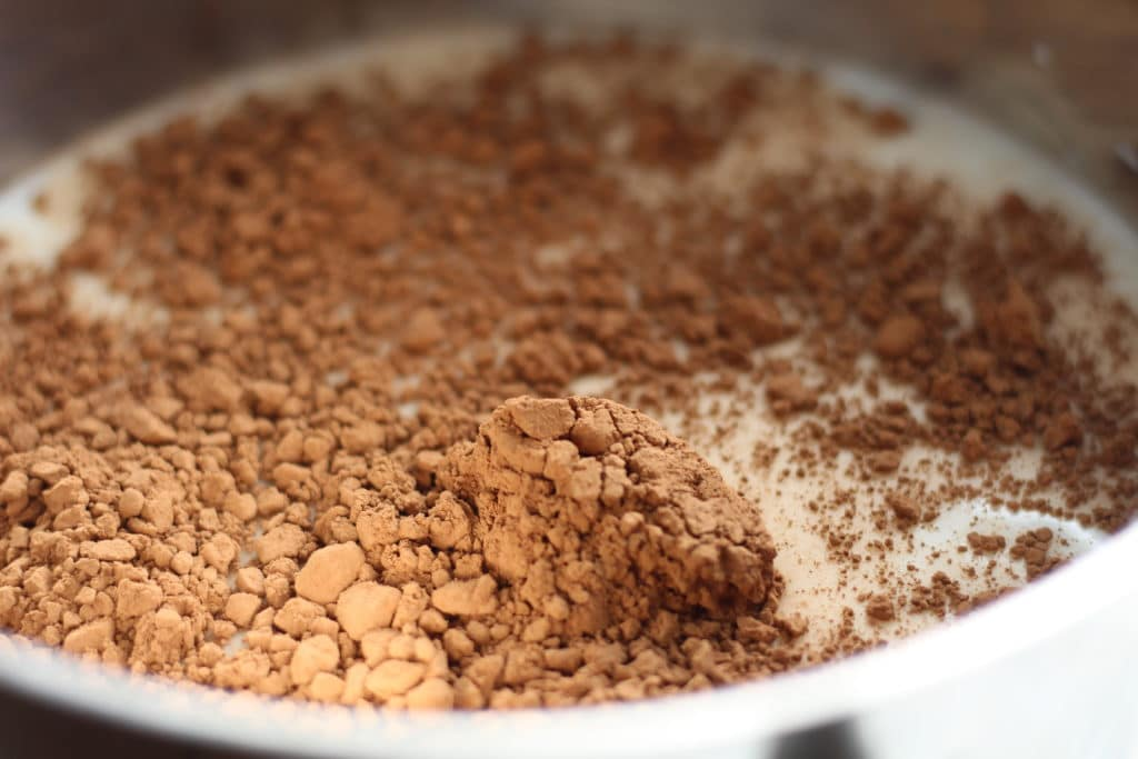 upclose shot of cocoa in pot with milk