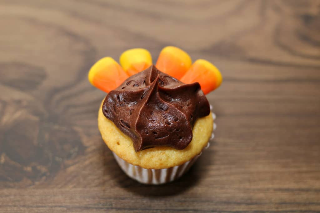 4 candy corns on top of chocolate icing creating a turkey cupcake