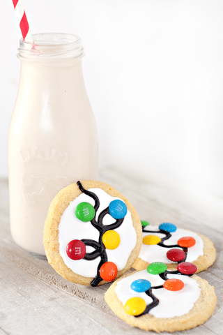 sugar cookies with white icing, gel icing and m&ms and a bottle of milk