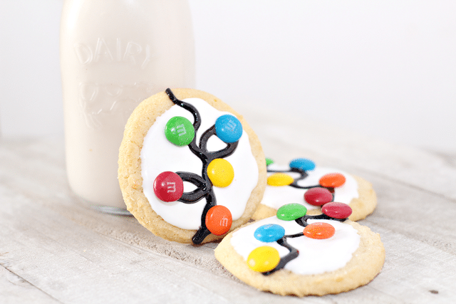 sugar cookies with white icing, gel icing and m&ms and bottle of milk