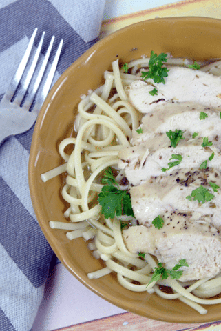 garlic lemon chicken over linguine with parsley, fork