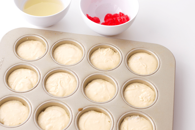 muffin tin filled with pineapple upside down cake mixture