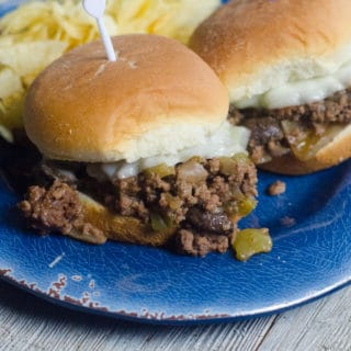 philly cheesesteak sliders with melted cheese and chips on plate