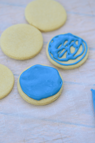 sugar cookies with blue icing on parchment paper