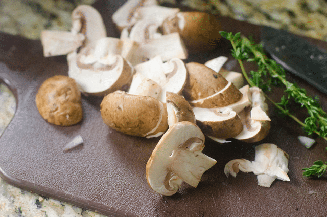 chopped mushrooms and thyme on a cutting board