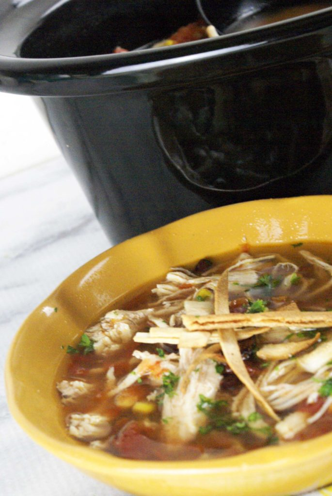 chicken tortilla soup in a bowl nect to a crock pot