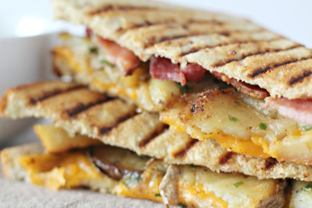 close up of loaded potato grilled cheese with bacon