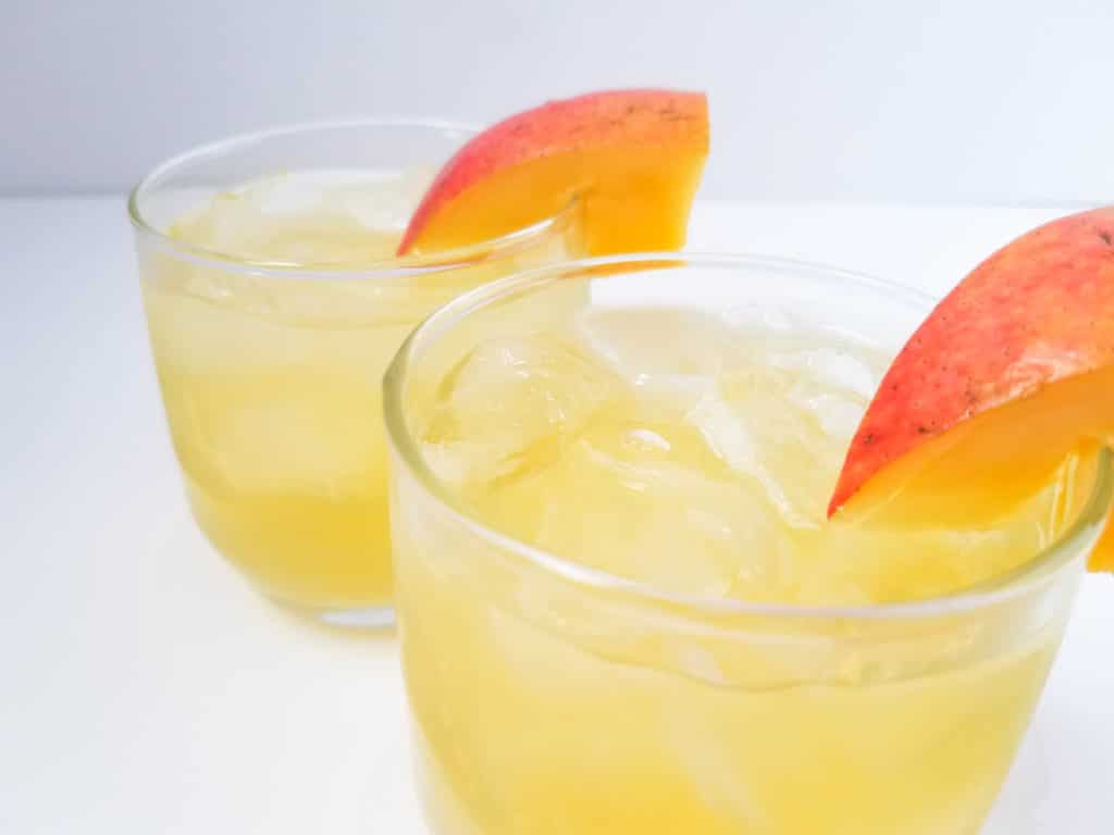 upclose of 2 glasses of mango vodka cocktail