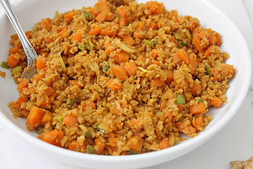 cauliflower fried rice in a bowl with a spoon