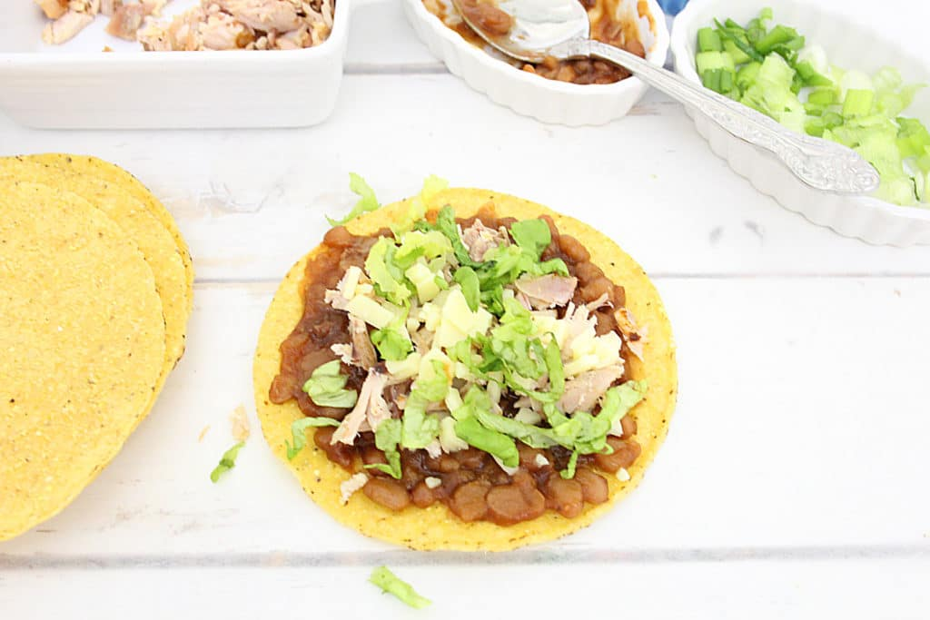 chicken, beans, cheese and lettuce on a tostada