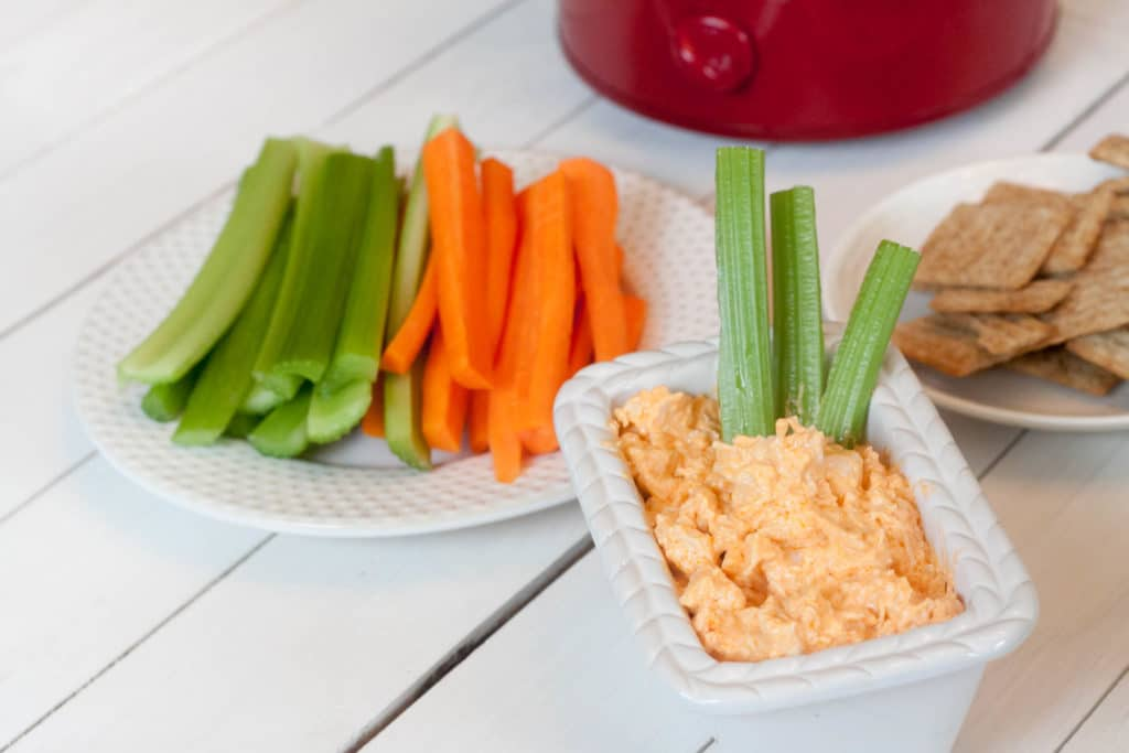 buffalo chicken dip with crackers, celery and carrots