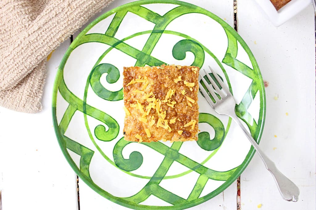 egg ham casserole with cheese on a green and white plate