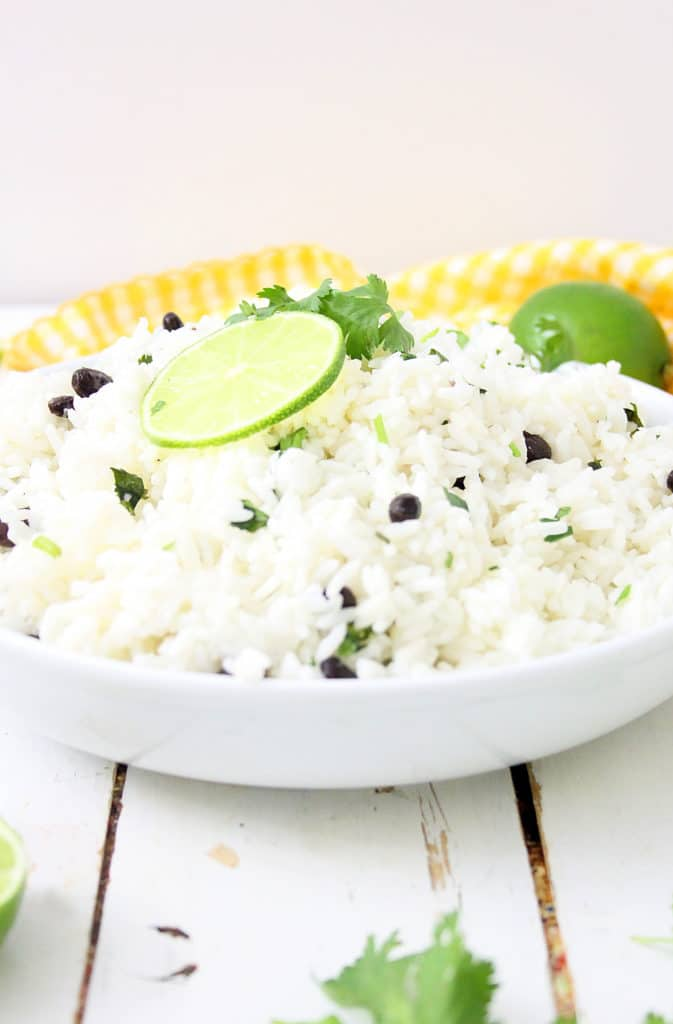 lime rice in a white bowl with limes on top