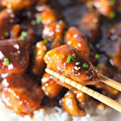 chopstick holding bourbon chicken piece